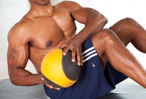 man doing trunk rotation with ball