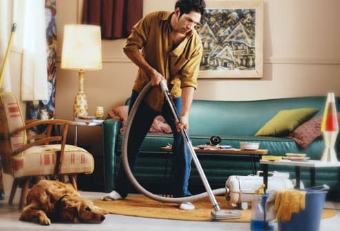 man vacuuming with labrador revtriever watching