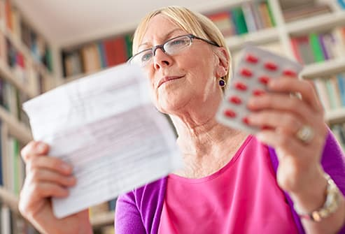 woman reading drug label
