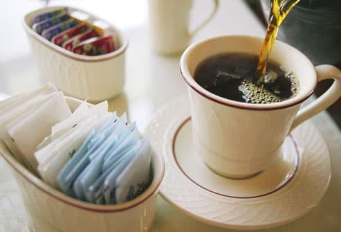 Fresh cup of coffee and sweeteners