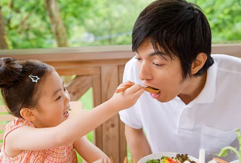 Daughter feeding veggies to dad