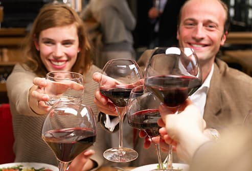 Smiling group toasting with red wine in restaurant