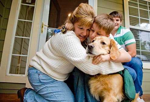 Mom hugging autistic son and guide dog