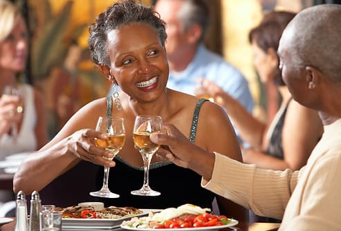 couple in restaurant toasting with white wine