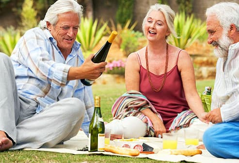 Three mature friends having  picnic with wine