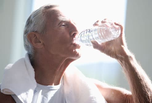 Senior man drinking water in gym