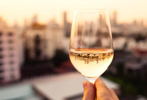 man holding glass of white wine close up