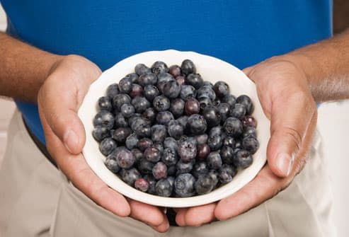 Man holding bowl of blueberries