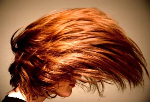 redheaded woman flipping hair