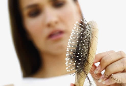 Concerned Woman Pulling Hair Out of Brush
