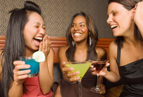 Three women holding drinks and laughing in bar