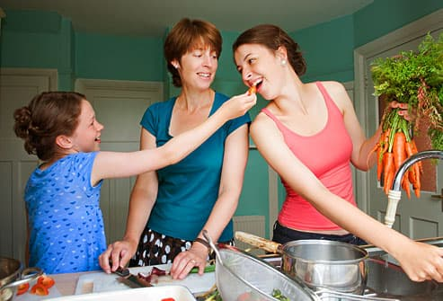 Mother and daughters preparing dinner together