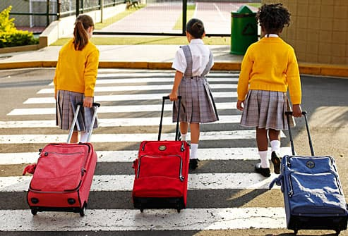 Three girls pulling book bags on wheels