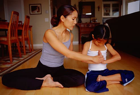 Mom teaching daughter a yoga pose
