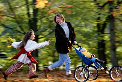 Woman and children running down forest path