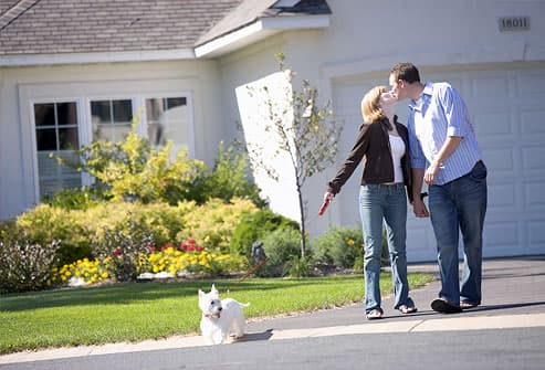 Couple kissing and walking dog