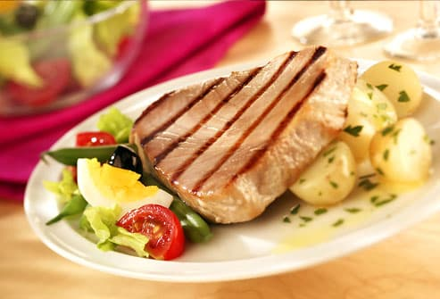 Grilled tuna steak with salad and potatoes