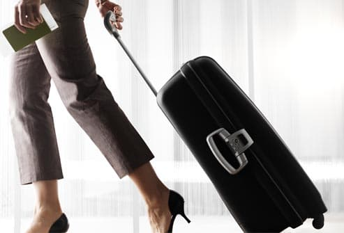 woman with roller suitcase in airport