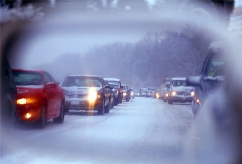 Traffic jam during snowstorm in side-view mirror