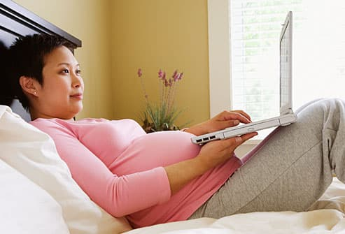 Pregnant woman researching hospitals online
