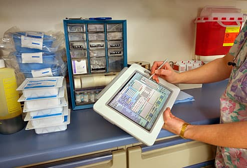 Nurse filling in patient data on electronic tablet