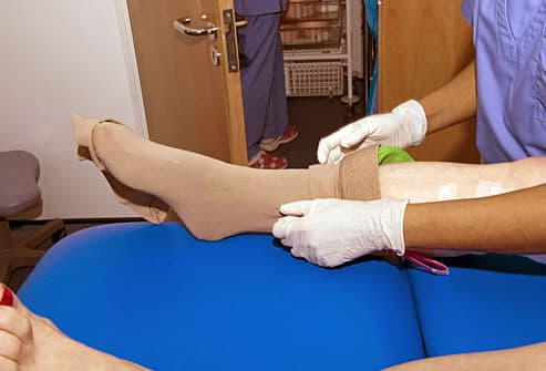 Nurse fitting patient with surgical stocking