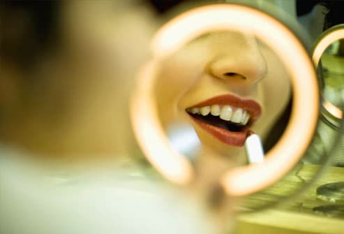 Woman applying lipstick in lit mirror