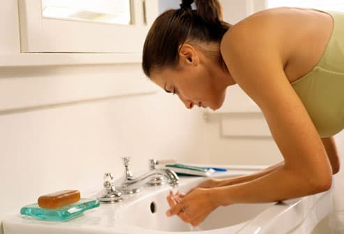 Woman wetting hands in sink