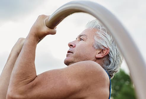 mature man doing pullups outdoors