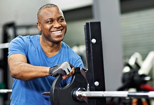mature man lifting weights in gym