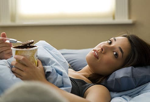 Depressed woman eating ice cream in bed