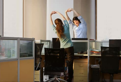 Office workers doing stretches late at night