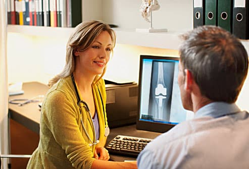doctor showing patient knee xray