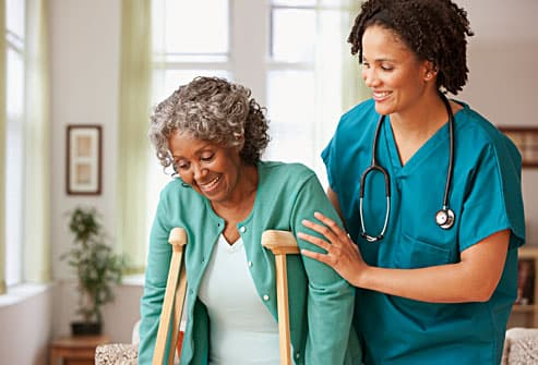 woman on crutches with home healthcare worker