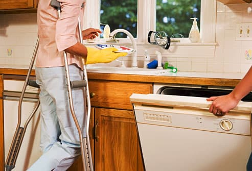 woman on crutches doing dishes