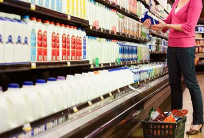 Woman shopping for lactose free milk