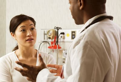 Profile of a male doctor talking to a young woman