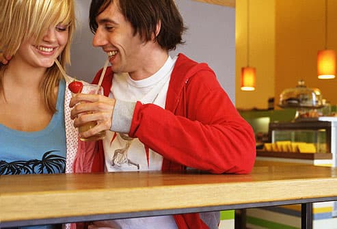 Young couple in cafe sharing drink through straws