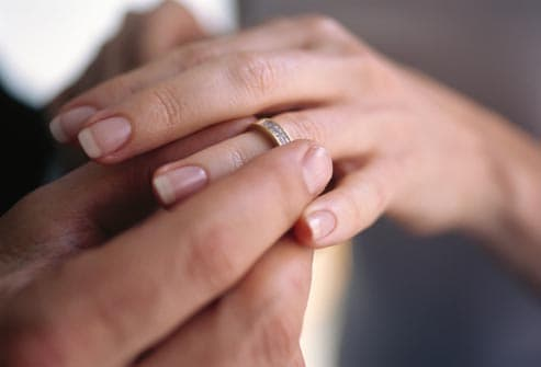 Man putting wedding  band on womans hand