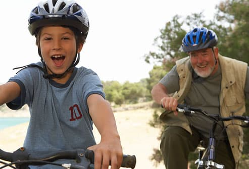 Grandfather and grandson riding bikes