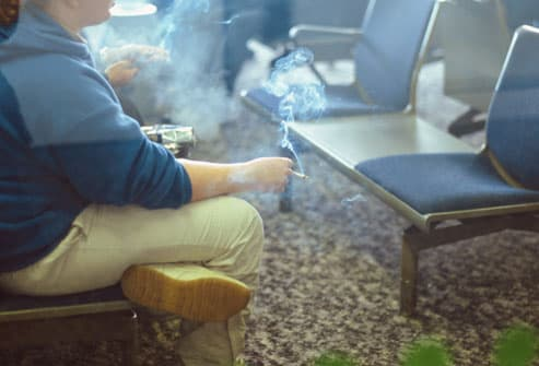 Woman Smoking In Airport Lounge