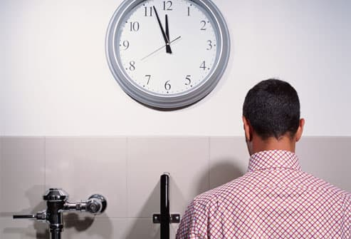 Businessman using urinal by big clock