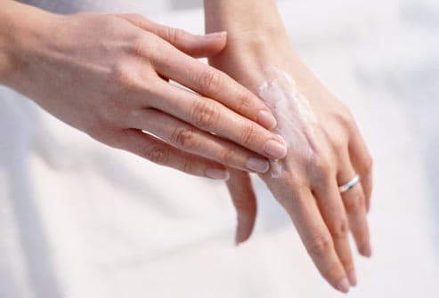 woman applying sunscreen to hands
