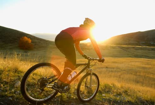 Woman riding mountain bike downhill at sunset