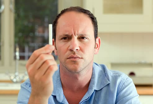 Balding man quizzically pondering a cigarette