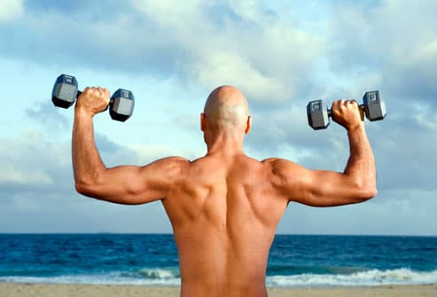 Bald man working with weights on beach