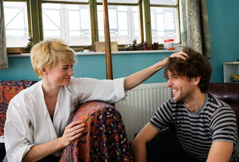 Woman playfully messing up her boyfriend's hair
