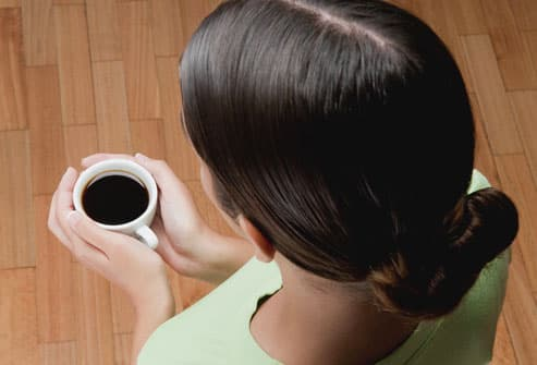 photolibrary rm photo of woman with coffee cup However, too much caffeine can lead to headaches when the stimulant effect ...