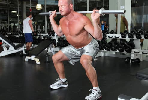 Trainer demonstrating squat with barbell