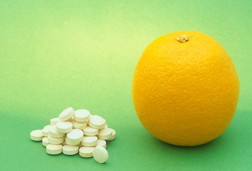 Vitamin C tablets and an Orange
